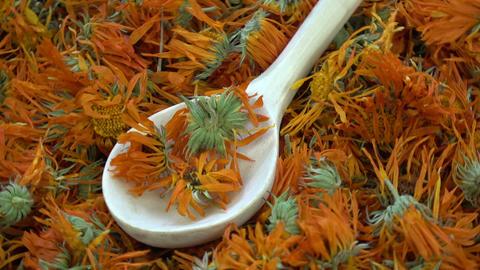 Rotating dried marigold calendula medical flowers background Archivo
