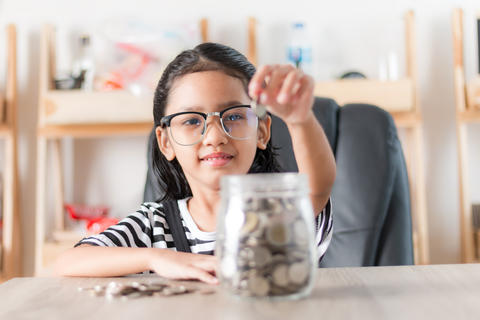 Asian little girl in putting coin in to glass jar for saving mon フォト