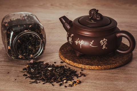 Asian teapot on stand and jar with scattering of tea Fotografía