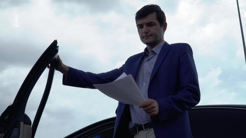 Businessman looks through business papers and sits in a car Footage