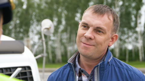 middle-aged smiling driver listens to road police inspector Footage