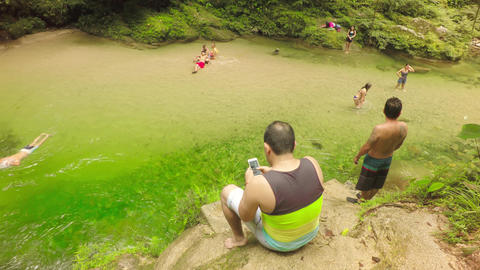 Adult Man Using A Mobile Phone In Front A Beautiful Natural Swimming Poll Live Action