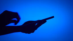 Black silhouette of woman hands shadow use smartphone touchscreen on blue Footage