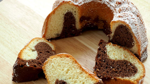 Traditional homemade marble cake. Sliced marble bundt cake on wooden table Live Action