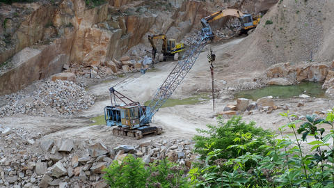 Mining in the granite quarry. Working mining machine - old crane and digger. Footage