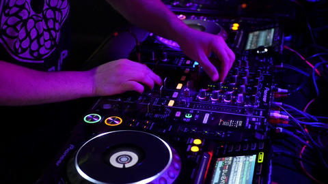 Dj playing electronic music on professional dj equipment - dj players with mixer ビデオ