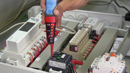 Hands of worker check contacts voltage indicator in electronics in factory Footage