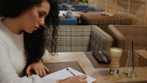 Cute brunette girl with curly hair is writing a poem in a restaurant 영상물
