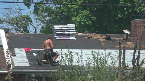 Man installing new shingles on roof Footage