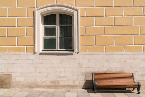 Empty bench against the wall with a window Photo