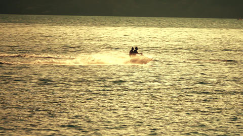 Two people riding jet ski at sea at sunset. Slow motion shot Footage