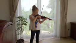 Young girl is practising playing viola Footage