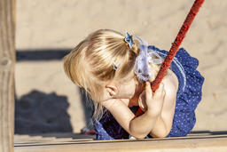 Young girl hanging on a swing at outdoor playground Photo