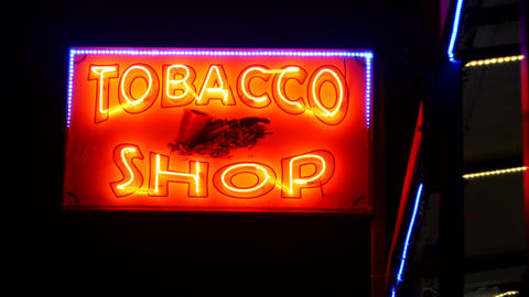 Tobacco shop glowing neon sign in the night Live Action