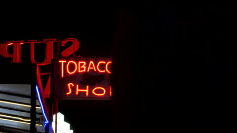 Tobacco shop neon sign glowing in the night Footage