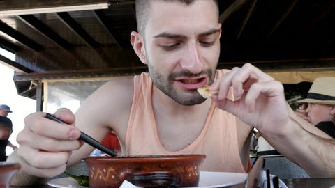 Young man eating a stew Archivo