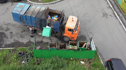 Worker of garbage truck loading container with garbage into its bins 영상물