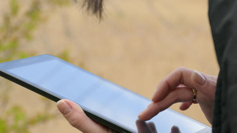 Close-Up Of Female Hands Using Tablet PC Outdoors Footage