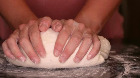 Close up of a young woman hand kneading a ball of bread dough Footage