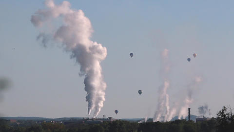A sped up shot of many hot air balloons in the sky near a factory Footage