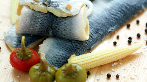 Saltwater marinated fish, cold appetizer. Herring fillet marinated on wooden Live Action
