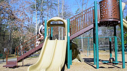 Young woman running, walking, climbing slide on children playground outside ビデオ