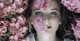 Close-up portrait of a girl lying on the ground with flowers of hydrangea on her Photo