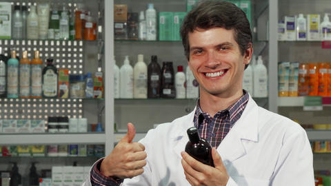 Cheerful pharmacist showing thumbs up while working at the drugstore Archivo
