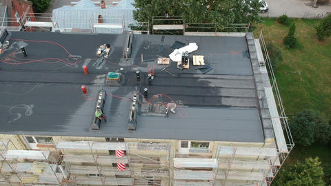 Workers repair old flat house roof, aerial view Live Action