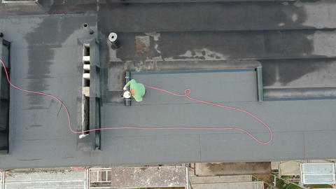 Worker on flat roof fixing waterproofing material, aerial Live Action