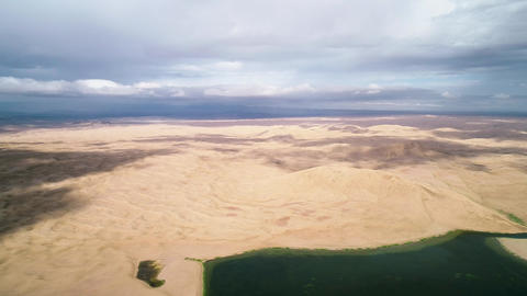 Panoramic view from above on a sandy desert with lakes. Flight over the barkhans Footage