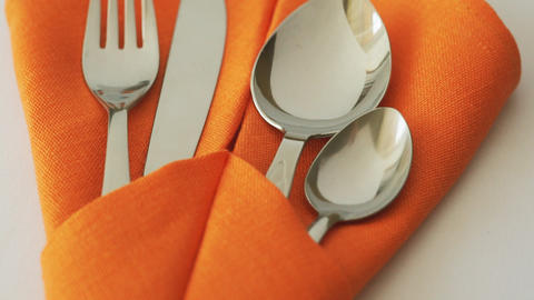 Cutlery set. Fork, knife, spoon and teaspoon in textile napkin on table Footage