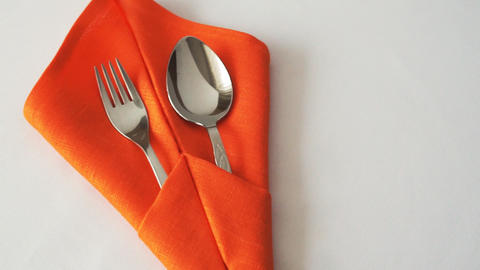 Fork and spoon. Fork and spoon in textile napkin on table GIF