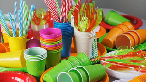 Colorful plastic disposable tableware for picnic on table Footage