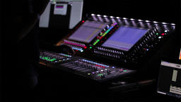 Digital sound board with DJ adjusting the volume and levels during a live Footage