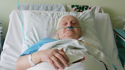 Old, ill woman in hospital bed Footage