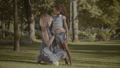 Loving mother bonding with her cute girl in park GIF