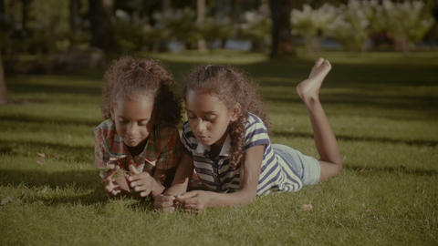 Happy cute sisters lying on green grass outdoors GIF