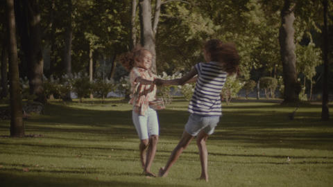 Joyful adorable sisters spinning in circle outdoors Footage