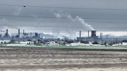 Apocalyptic view at smoking chimneys nex to farmland. Air and soil contamination ビデオ