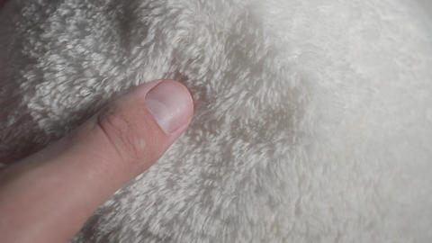 Closeup of a hand taking syntheticpolyester fur Live Action