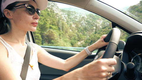 Beautiful young woman driving a car in Mediterranean scenery GIF