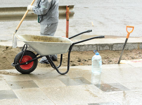 The worker brings on a construction wheelbarrow sand for laying paving slabs フォト