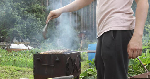 Man blows coals in a fire with shovel for fire Footage