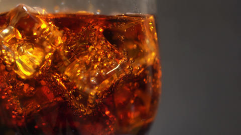 Cola in the glass with Ice cubes and bubbles rotating. Food background. Soda Archivo