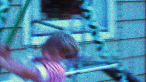 1967: Confident boy swings high on swings too close to house Footage