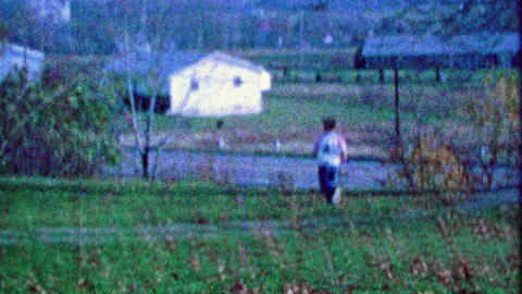 1967: Boy runs autumn leaf pile rural country living style Footage