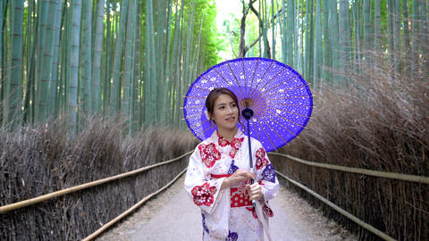 Asian woman wearing japanese traditional kimono at Bamboo Forest in Kyoto, Archivo