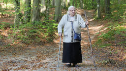Old woman with a walking stick on a walk in park Live Action