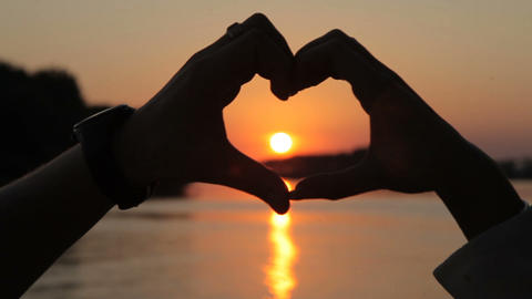 Symbol of love, heart from the hands of lovers at sunset Footage